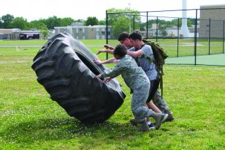 Three cadets practice flipping a tire.