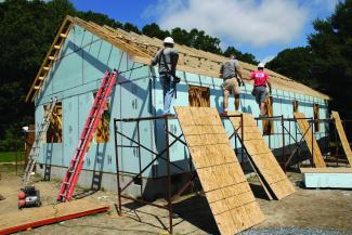 Volunteers work to set rafters on a Habitat home in Milton.